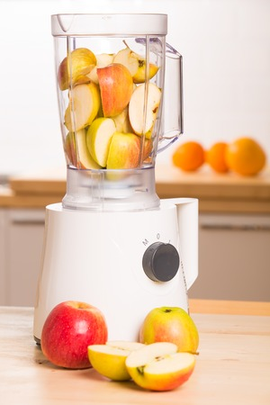 Blender with apples in the kitchen  Close up photo