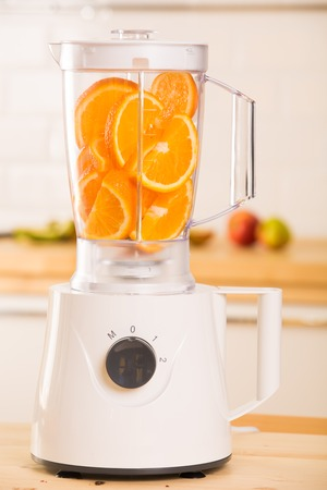 White blender with juicy oranges on a wooden table in the kitchen photo