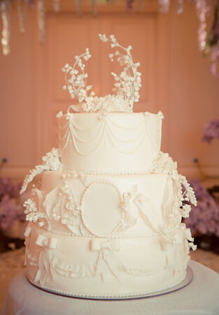 Beautiful white wedding cake, decorated with lilies of the Valley photo