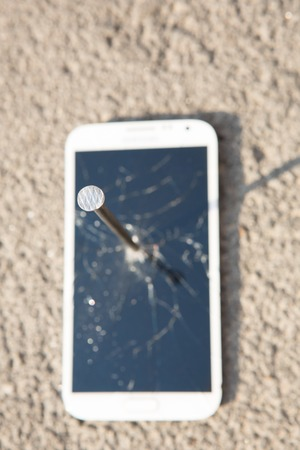 portable failure: metal nail and smartphone with a broken screen over the stone surface