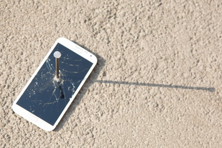 metal nail and smartphone with a broken screen over the stone surface photo