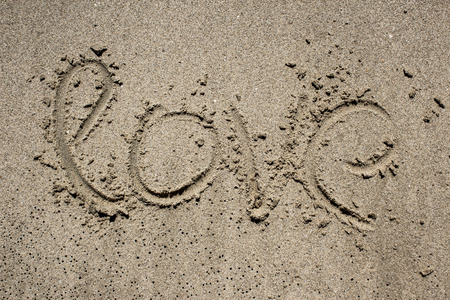 valentine s day beach: inscription on the sand near the sea and the waves - LOVE