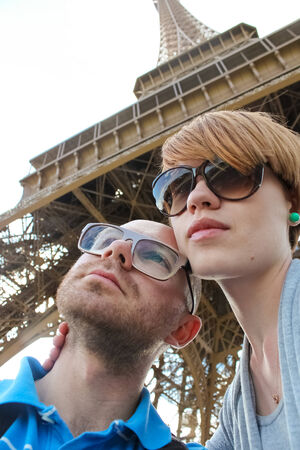 Side view of a young couple embracing with Eiffel Tower in distance Stock Photo