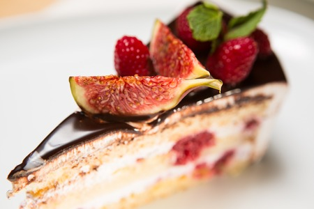 cake with chocolate, fig and raspberry decorated mint leaves photo