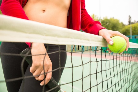 young woman with yellow ball and racket near net photo