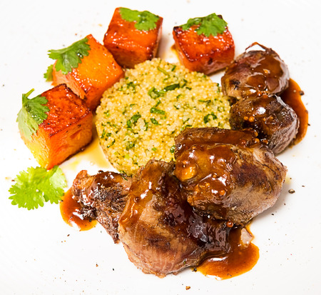 Organic meat of lamb cooked with slices of pumpkin and quinoa in oriental style on a white plate photo