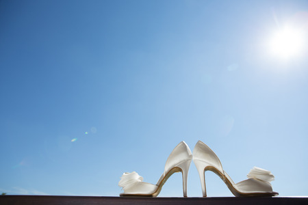white wedding shoes with a bow . Close up photo