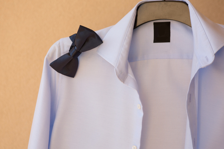 groom shirt on a hanger with a bow tie photo