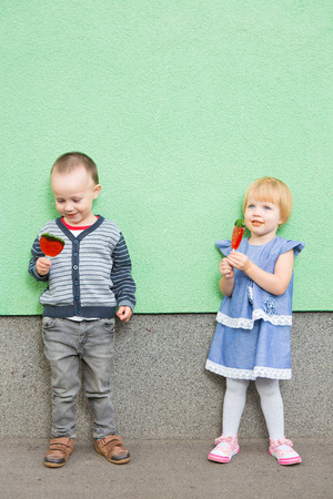 Adorable little girl and boy with colorful lollipops photo