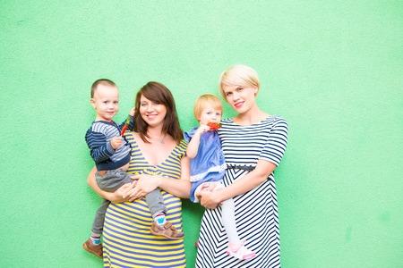 lesbianas: dos hermosas chicas con unos ni�os en el fondo verde Foto de archivo