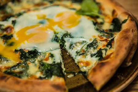Margarita pizza with arugula and egg for breakfast, selective focus photo