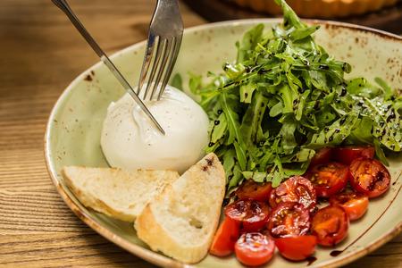 Burrata mozzarella cheese, tomato and bread, selective focus Stockfoto
