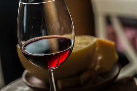 scamorza cheese: Red wine in wine glass with cheese. Selective Focus. Focus on the front of the rim of the wine glass