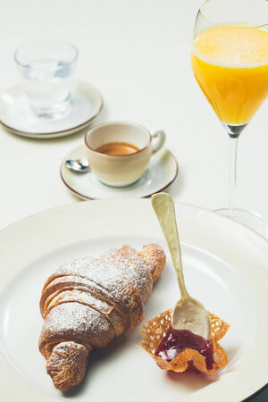 colores calidos: breakfast with croissant,coffee and juice. Warm colors. Shallow dof.
