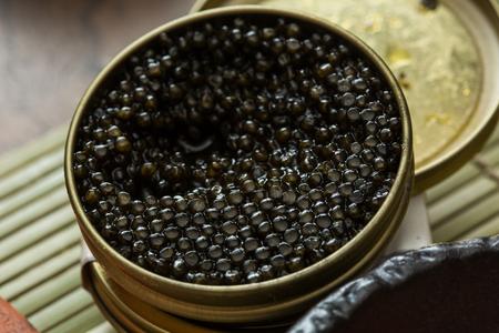 Black caviar in small round metal tin on ice Standard-Bild