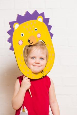 Little blonde girls holding hedgehog mask on white background photo