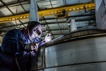 Man welding with reflection of sparks on visor. Hard job. Construction and manufacturing 스톡 콘텐츠