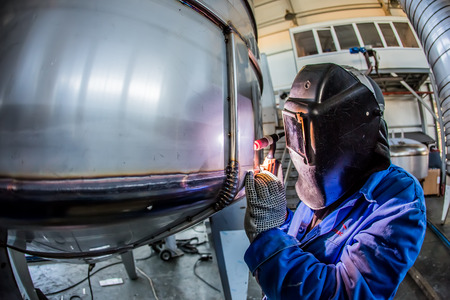 Man welding with reflection of sparks on visor. Hard job. Construction and manufacturing Standard-Bild