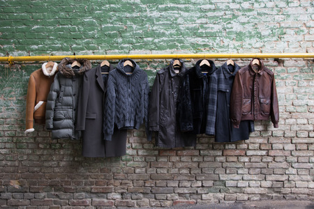 Men's trendy clothing on grunge brick wall. Concept background Фото со стока