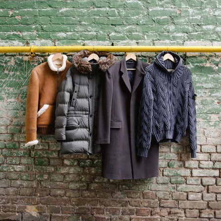 winter clothes: Men's trendy clothing on hangers on grunge brick wall. Concept background