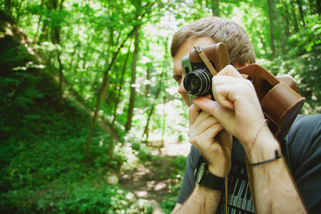 prime adult: Closeup of young hipster man with digital camera outdoors. Young male photographer photographing nature Stock Photo