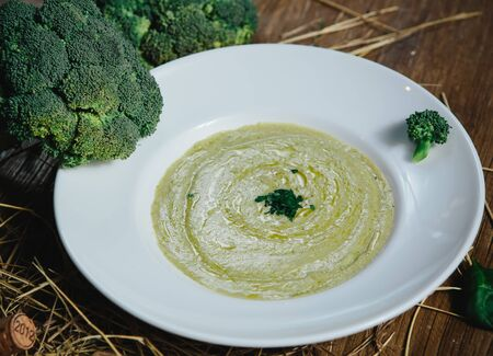 Broccoli cream soup and ingredients on table photo