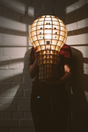 Hanging, wooden light shade lamp with bulb in hands photo