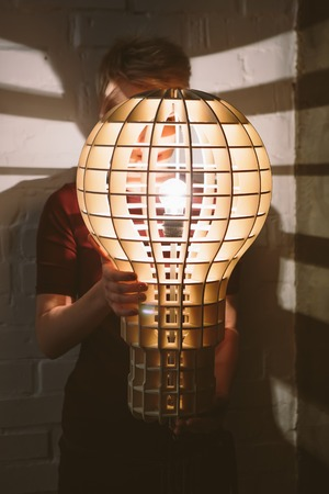lamp shade: Hanging, wooden light shade lamp with bulb in hands