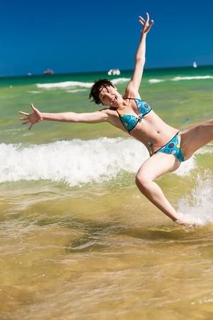 Yong happy woman splashing water in the ocean photo