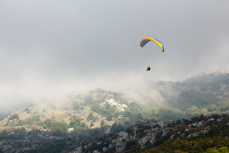 paraglide: The Paraglide silhouette over mountain peaks. Montenegro