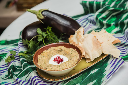 Traditional arabian eggplant dip baba ganoush with herbs and smoked paprika on a wooden background
