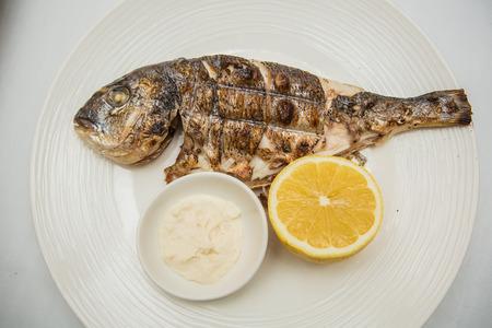 dorada: Grilled organic dorada fish with lemon on white dish Stock Photo
