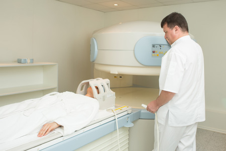 x ray machine: doctor examining woman at Magnetic resonance imaging
