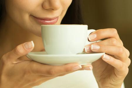 コーヒー。美しい少女は、カフェでお茶やコーヒーを飲みます。ホットド リンクのカップと美モデル女性。温かみのある色調のトーン