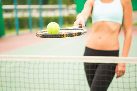 avocation: young woman with yellow ball and racket near net