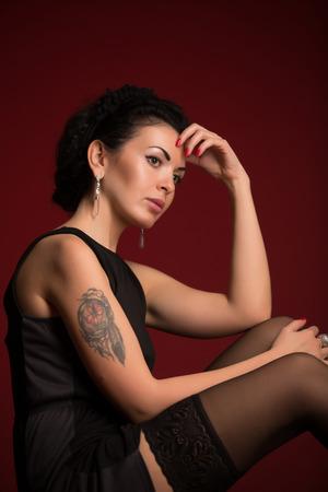 Studio portrait of a sexy brunette in black lingerie, stockings Stock Photo