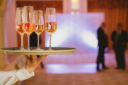 formal dinner party: Waiter serving champagne with strawberries on a tray Stock Photo