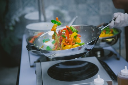 Chef cooking vegetables in wok pan. Shallow dof