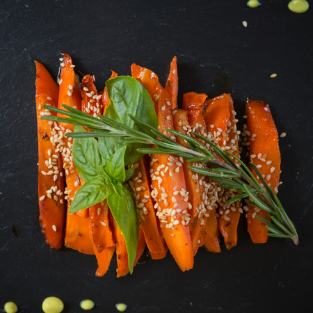 caramelized: Caramelized carrots on black table. Shallow DOF Stock Photo