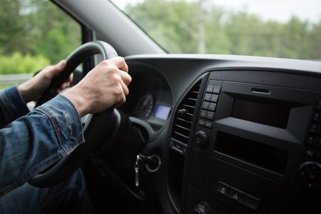 hand close up of a man driving a car