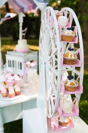 Dessert table for a party. Cake, cupcakes, sweetness and flowers. Shallow dof Archivio Fotografico