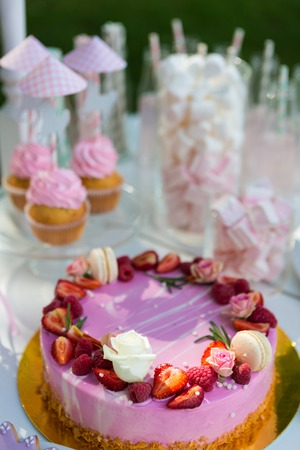 Dessert table for a party. Cake, cupcakes, sweetness and flowers. Shallow dof Stock Photo