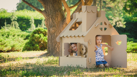 sister: Two funny kids are playing in a cardboard toy house. In a summer day in the park