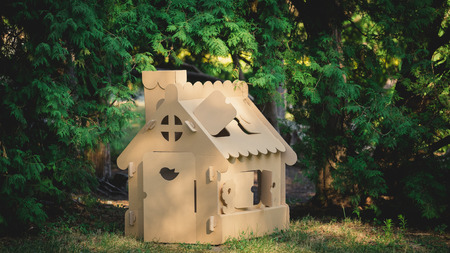 citypark: Toy house made of corrugated cardboard in the city park on the grass. The concept of eco-estate