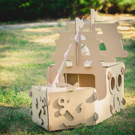 city park boat house: Cardboard toy boat in the park. Eco concept Stock Photo