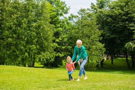 citypark: Portrait of happy mother and baby playing outdoors Stock Photo