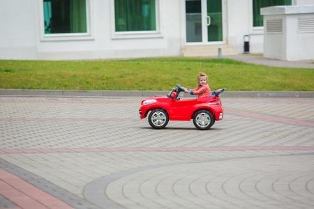 美しい小さな女の子乗馬グッズ車夏都市公園。