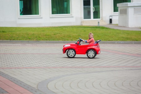 Beautiful little girl riding toy car in summer city park.