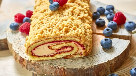 homemade cake: bright colorful cake roll on wood with berry. Shallow dof