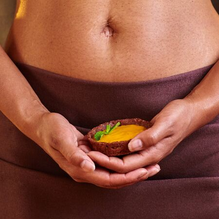 temptation: Dessert in the hand at the level of the abdomen. Temptation concept